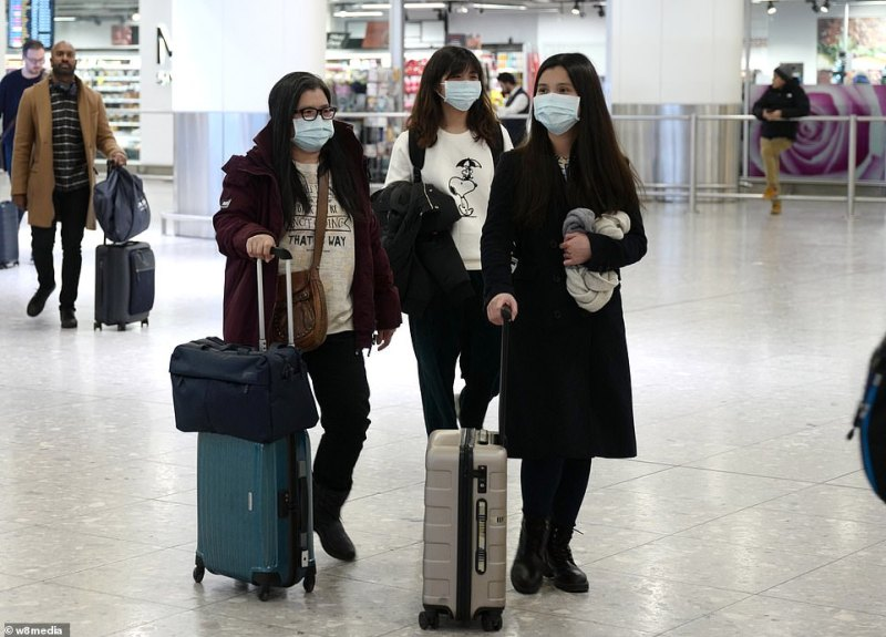 An undated photo shows passengers arriving at Heathrow airport wearing face masks.British expats demanded the Government 'get us out of here'. One who was trapped in Wuhan told fellow Britons: 'London thinks you're all dead!'