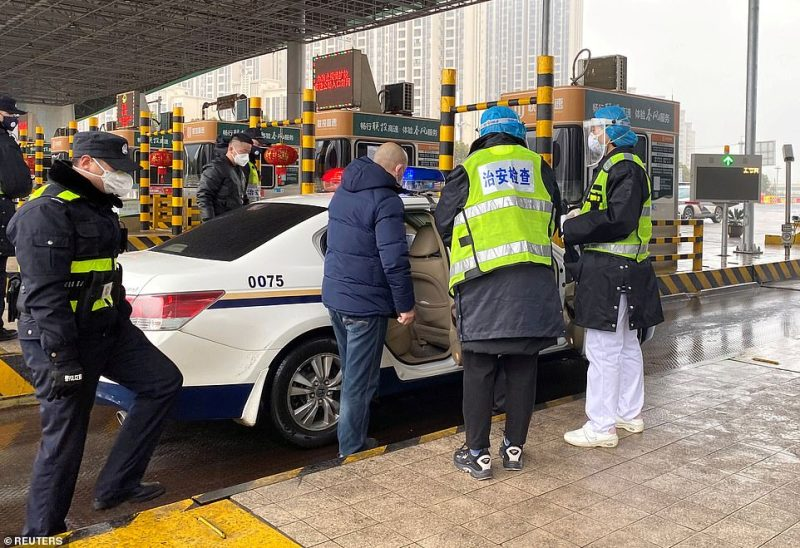 Police officers wearing masks today checked a car for smuggled wild animals at an expressway toll station outside of Wuhan, on the eve of the Chinese Lunar New Year celebrations