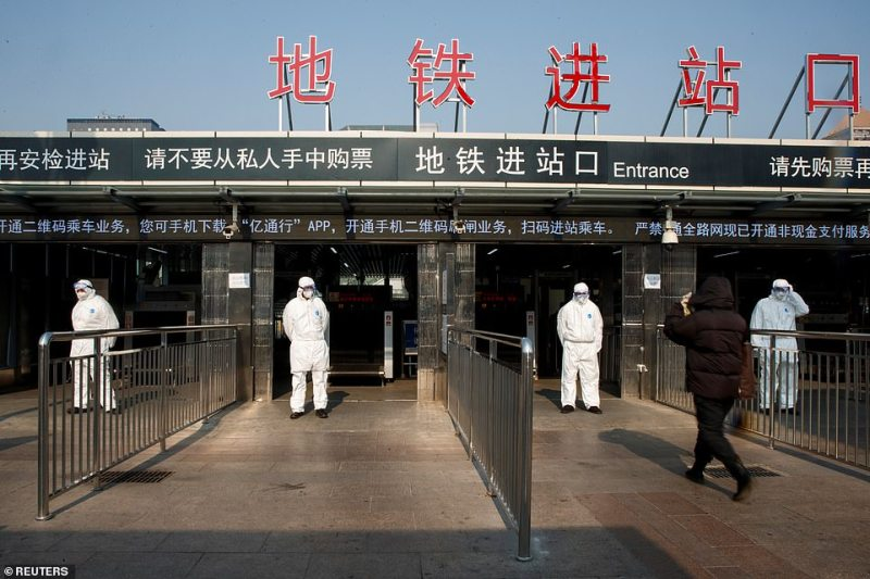 Workers take the body temperature of passengers before they enter the subway station outside Beijing Railway Station today.Some 56 million people are now subject to restrictions on their movement as authorities expand travel bans in central Hubei province, now affecting 18 cities