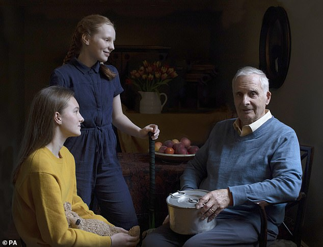 Steven Frank, 84, with his two granddaughters Maggie, 15, and Trixie 13, was photographed holding a pan his mother used as a boy