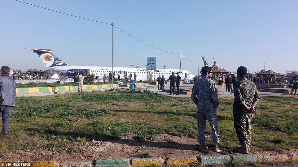 Security officials inspect the scene after a Caspian Airlines plane crashed off the runway inMahshahr on Monday morning