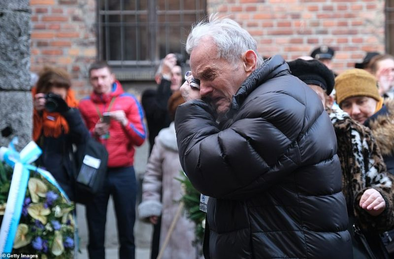 A member of the delegation breaks into tears in front of the extermination wall. Despite it being 75 years since the camp's liberation the memories are still raw for many of the survivors who not only endured the torture of living through years inside, but also lost many of their loved ones