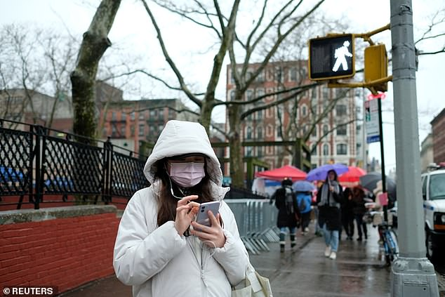 Pharmacies across the US have reported that they've sold out of face masks amid fears of coronavirus as the infection continues to spread across the globe, already sickening five Americans. Pictured: A woman wears a face mask in Chinatown, New York on Saturday