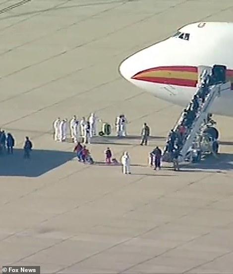 Urzędnicy w kombinezonach hazmat spotykali pasażerów, gdy wysiadali z samolotu i czekali na autobusy