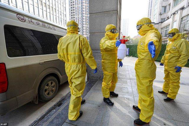 Kilka krajów odradza zbędne podróże do Chin.  Nz. Pracownicy pogrzebu dezynfekują się po obchodzeniu w czwartek ofiary koronawirusa w Wuhan