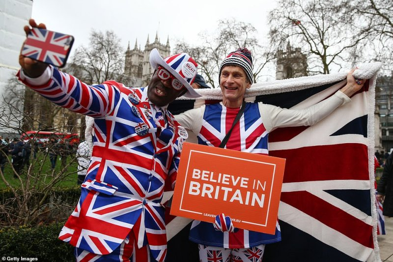 Pro Brexit supporters pose for photos at Parliament Square, London this afternoon. One holds a placard which reads 'believe in Britain' ahead of this evening's festivities