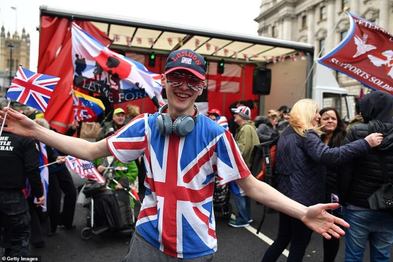 Pro-Brexit supporters wave Union Jack flags while standing on a European Union flag at Parliament Square as people prepare for Brexit in London