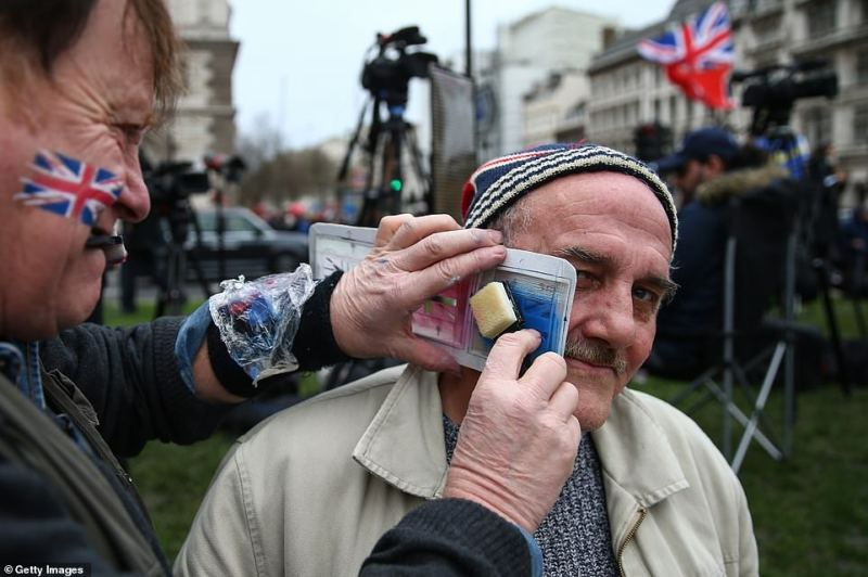 A pro-Brexit supporter has a Union Jack painted onto his face at Parliament Square ahead of festivities this evening