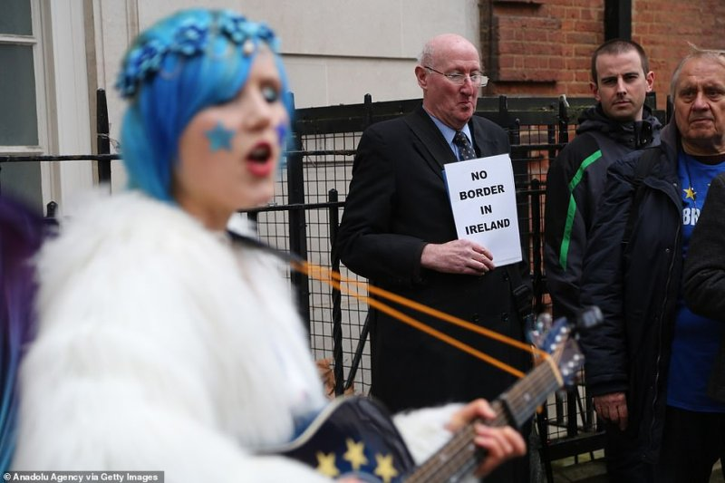 A woman with a blue wig and a guitar plastered with the European flag performs in front of a man with a sign that reads 'no border in Ireland