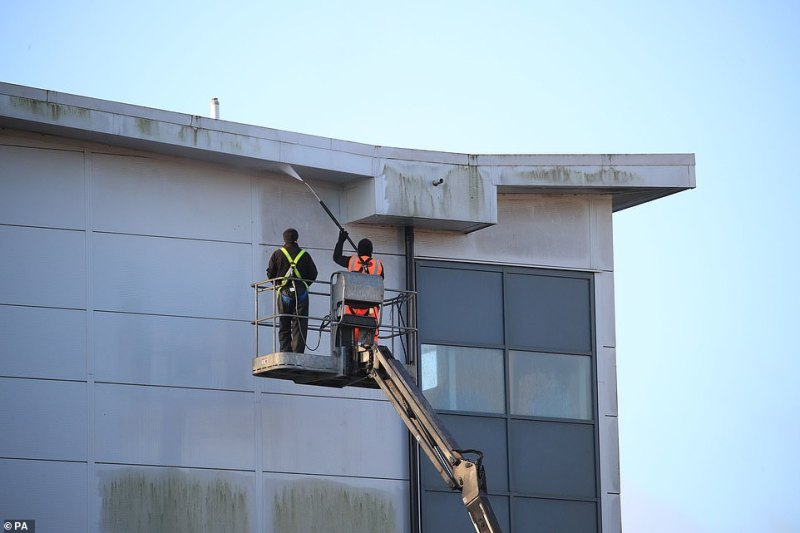 Cleaners use a jet wash to clean the outside of ablock at Arrowe Park Hospital in Merseyside today. The outside of the building appears as if it hasn't been washed in some time - but is now suddenly getting a sprucing up as British evacuees from Wuhan are set to stay for 14 days