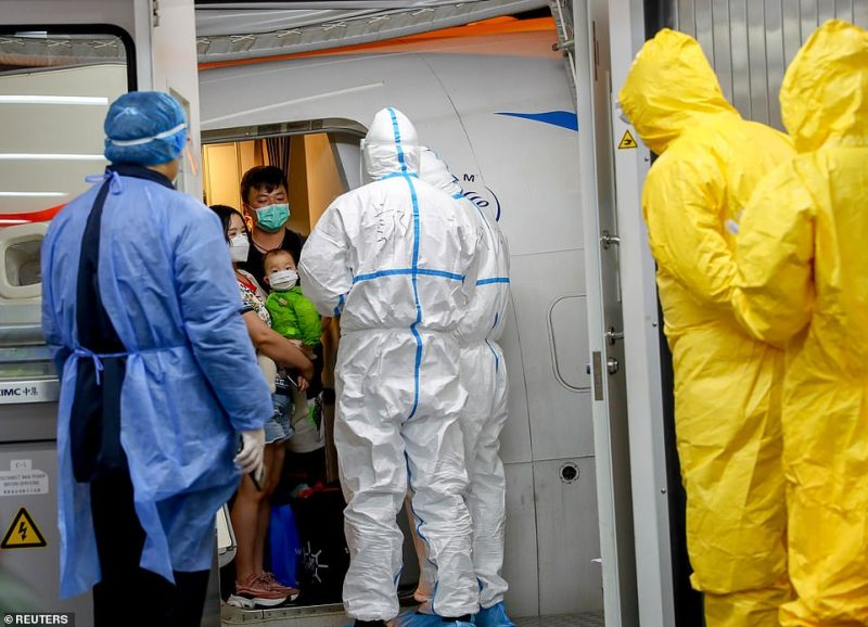 Health officials wearing full protective clothing greeted passengers arriving on a Xiamen Airlines flight from Thailand to Wuhan Tianhe International Airport