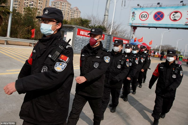 Security guards walk in formation after changing shift at a checkpoint at the Jiujiang Yangtze River Bridge in Jiujiang, Jiangxi province, China, as the country is hit by an outbreak of a new coronavirus