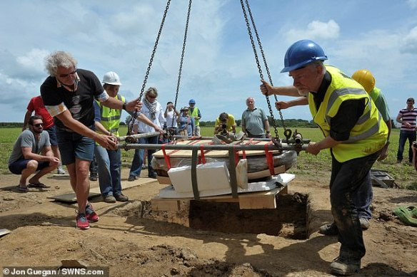 The block of coins is pictured being lifted out of the ground. Metal detectorist Reg Mead is pictured left wearing the black shirt