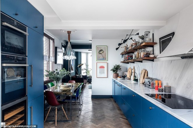 Ed O'Donnell, an interior designer, and his partner JP Banks have transformed their narrow 10ft-wide London townhouse into a spacious home by using clever tricks to make use of every nook and cranny (pictured, the couple decided to knock down a wall separating the kitchen and living room to open up the space - perfect for the couple to entertain guests in)