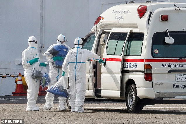 Health workers wearing protective suits carry bags to an ambulance near the cruise ship Diamond Princess today, which is anchored and being held in quarantine near Daikoku Pier Cruise Terminal in Yokohama