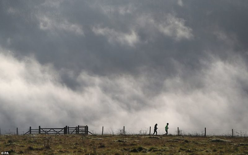 Two joggers make their way across Butser Hill near to Petersfield in Hampshire this morning