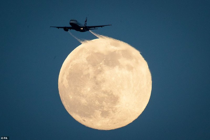 London's Gatwick and Heathrow airports have both seen disruption, leaving many passengers faced with hours of chaos. Pictured: A British Airways flight sweeps across a magnificent image of a super snow full moon, the name given to the time of the month when the satellite is closest to earth
