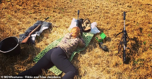 Rikke pictured lying on the floor in hunting position using her shotgun
