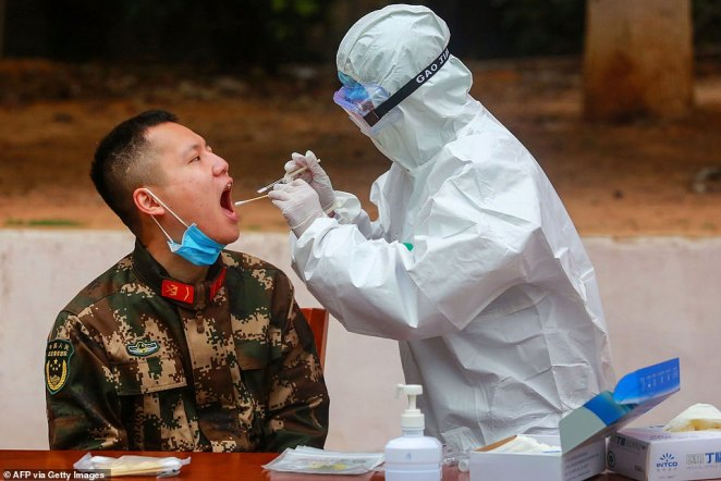 Medical staff members collect samples from Chinese paramilitary police officers to be tested for coronavirus in Guangdong