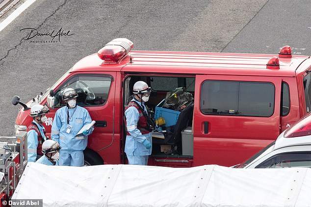 Officials in protective suits, masks and helmets work by the side of a van which is parked at Yokohama port, where the Diamond Princess is under quarantine