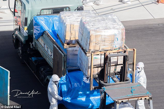 Supplies are lifted from the back of a truck in Yokohama, where passengers are bracing for a second week in quarantine