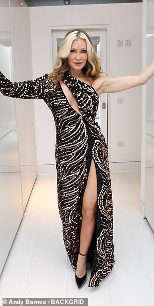 Turning heads: Another sexy ensemble was a floor-length sequinned gown that featured a racy thigh high slit and slash across the bodice