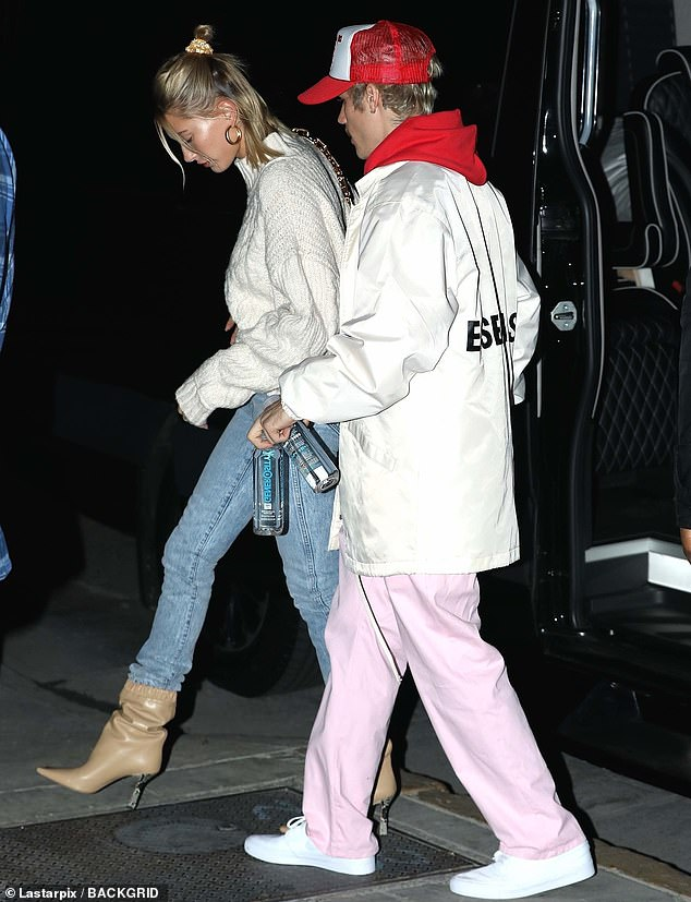Low key:Justin was more casual with a white jacket over a red hoodie and baggy pink pants. He sported a red and white trucker had and the mustache he's worn in recent weeks