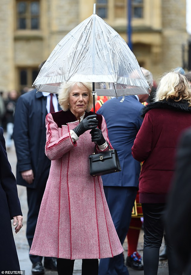 The Duchess of Cornwall holds on to an umbrella as she shields herself from the bitter cold rain at the Tower of London today