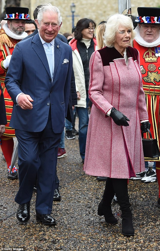 The Duchess of Cornwall wrapped up warm in a statement pleated overcoat (pictured) and carried an umbrella as she joined Prince Charles for a tour of the Tower of London today