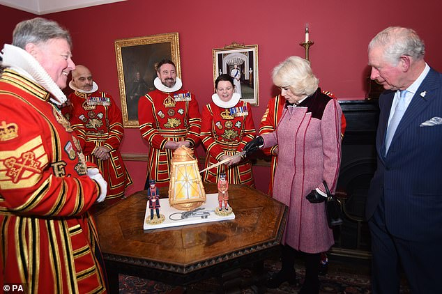 The Duchess of Cornwall laughed along with a group of Beefeaters as it was joked 'We'll get you a job as an executioner' when she cut into a lantern-shaped cake at the Tower