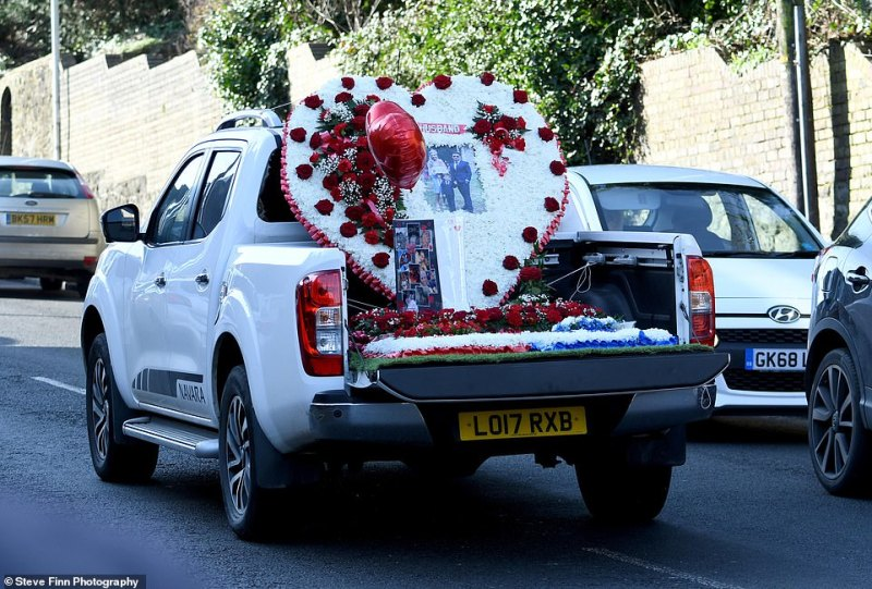 A pick-up truck joined the funeral procession covered in red, white and blue floral tributes to Joe, with the word 'husband' and a picture of him, his estranged wife Charmaine, and two children