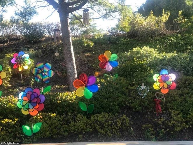 Newly planted purple and yellow flowers, which are representative of Bryant's Lakers team colors, surround the graves, as do 'love' balloons and colorful flower pinwheels - which signify a child's death