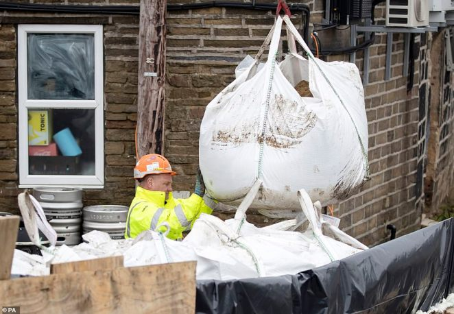 Workers in the Calder Valley towns of West Yorkshire (pictured today) are already trying to recover from the devastating effects of Storm Ciara, but are using sandbags to prevent further damage to the area with Storm Dennis looming tomorrow