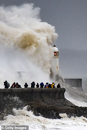 Waves are seen crashing against the harbour wall in in Porthcawl, Wales yesterday