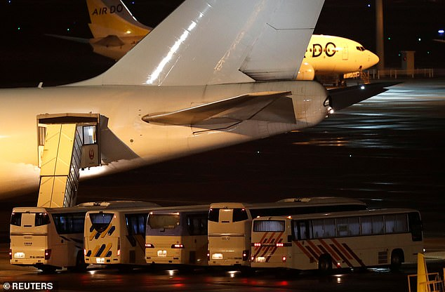 Buses believed to carry the U.S. passengers of the cruise ship Diamond Princess, where dozens of passengers were tested positive for coronavirus, are parked next to an airplane in Yokohama