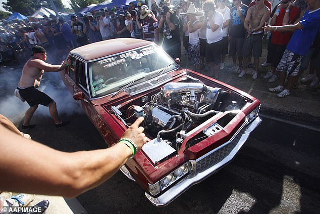 A spectator holds on to a car performing a burnout on Tuff Street during the Summernats car festival in Canberra in 2012. Holdens will become increasingly rare on the young street scene with its planned demise