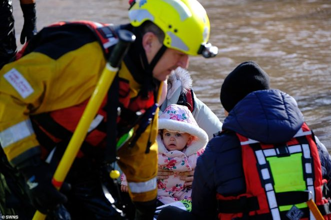 A baby is pictured being rescued from flooded homes in Hereford today after water levels at the Old Wye Bridge reached dangerous heights