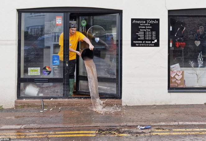 A young man empties a bucket of water from a shop in Crickhowell, Wales, which was almost completely underwater after Storm Dennis battered Powys