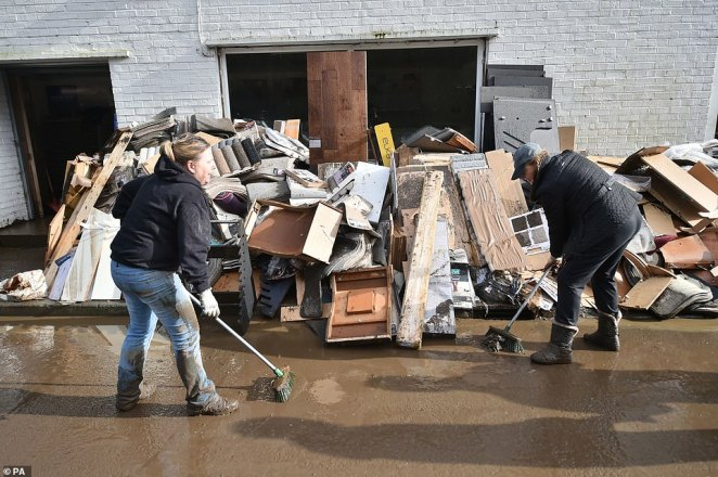 Staff members cleaning outside the Celtic Flooring store, which has been damaged by floodwater in Nantgarw, South Wales