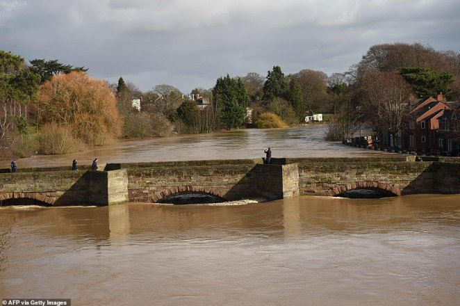 People are seen walking on the Old Bridge in Hereford, as the waters of the swollen River Wye fill the arches below