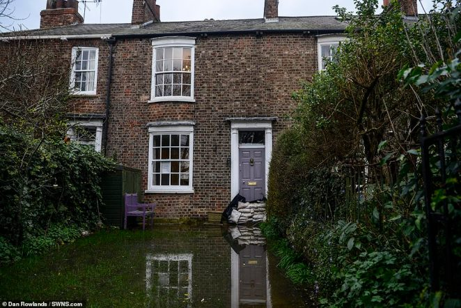 A terraced house is pictured with sandbags at the front door in York after being inundated with flood water