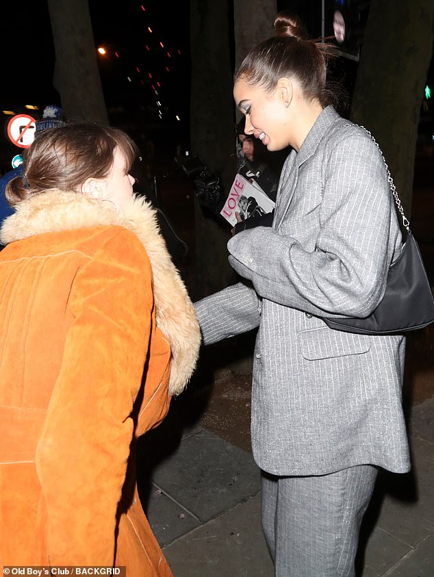 Friendly: She pulled her glossy brunette tresses into a sleek braided topknot for the occasion