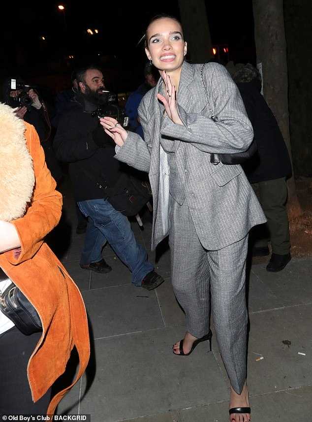 Stylish: Hana Cross, 23, was oozed sartorial chic in another grey trouser suit on Tuesday night, as she made an animated exit from LOVE Magazine's annual party at London Fashion Week