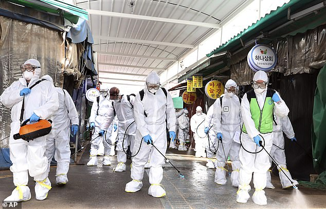 Workers wearing protective suits spray disinfectant as a precaution against the coronavirus at a market in Bupyeong, South Korea