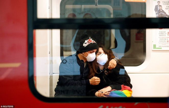 A couple wearing face masks is seen in the subway in Duomo underground station in Milan