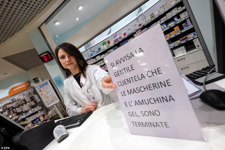 A pharmacist puts out a sign informing customers that they have sold out of protective masks and sanitising gel in Palermo