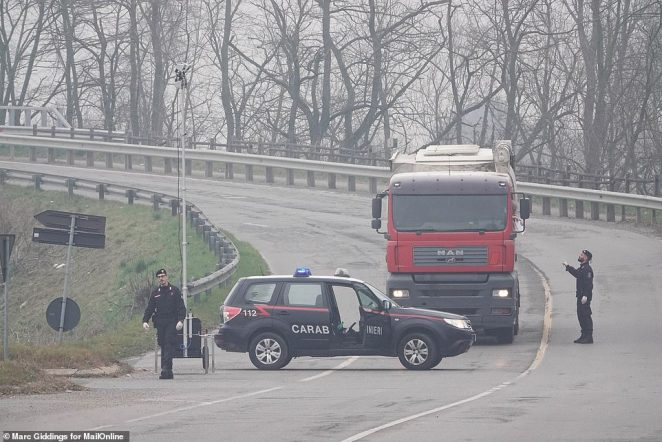 Police turn back a truck driver attempting to find his way around the quarantined red-zone covering parts of Lombardy, in northern Italy