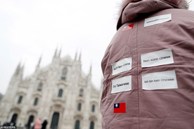 A tourist from Taiwan wears stickers on her back announcing that she is not from China while visiting Milan's cathedral