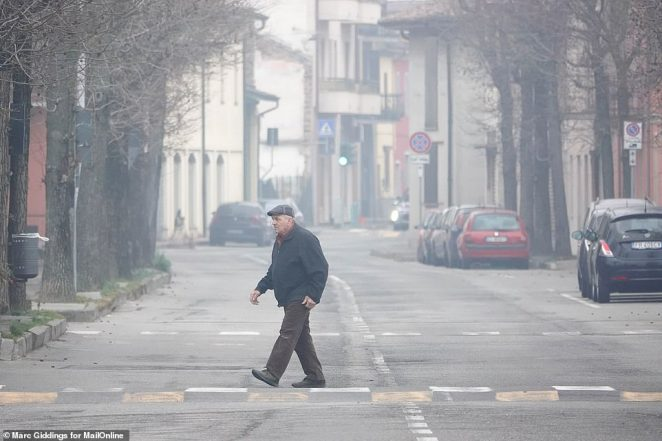 A man walks across the street in one of the zones of Lombardy which has been hit with restrictions as health authorities try to contain the spread of coronavirus