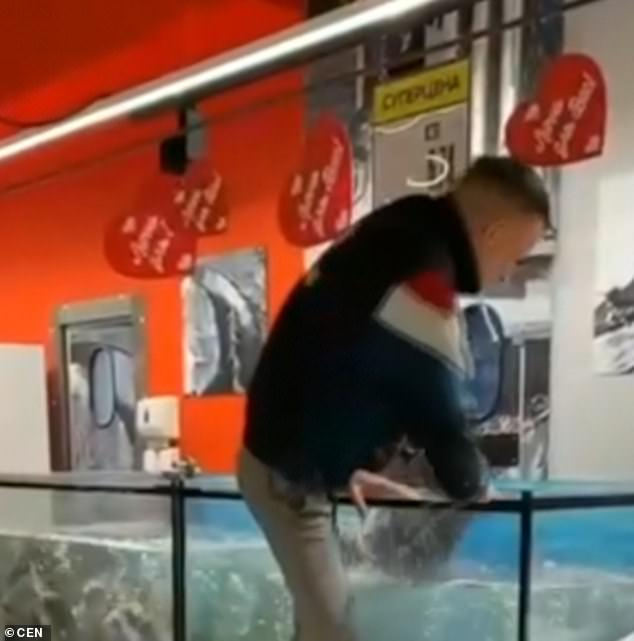 Footage shows the unnamed man pointing at an object lying at the bottom of the tank in a supermarket in Almi shopping centre in the city of Gomel in south-eastern Belarus